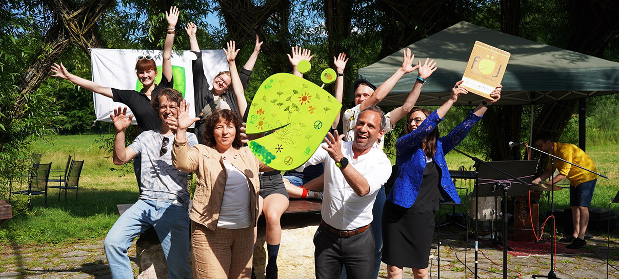Das Bild zeigt Umweltminister Glauber mit einer Gruppe jubelnder Jugendlicher, die das Schild FÖJ hochhalten