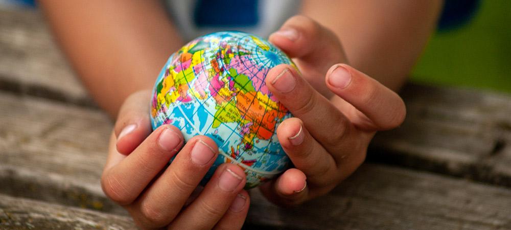 Kinderhände halten kleinen, bunten Globus